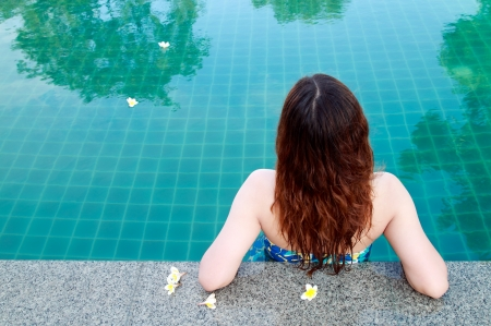 beautiful woman resting on the edge of swimming pool