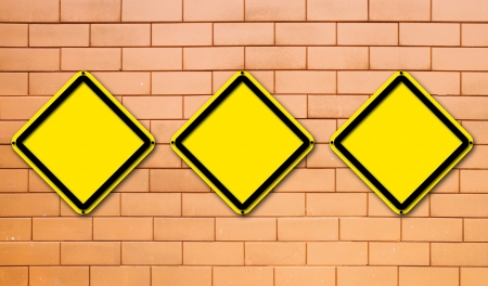 Three blank yellow traffic sign on brick wall background photo