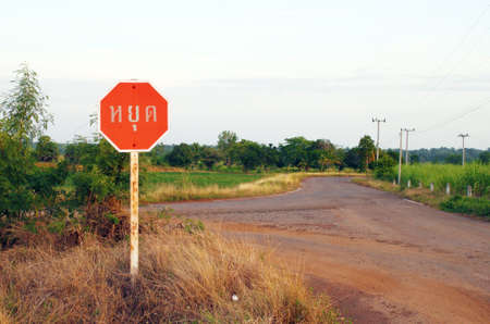 stop sign in a country road (Thai language) photo
