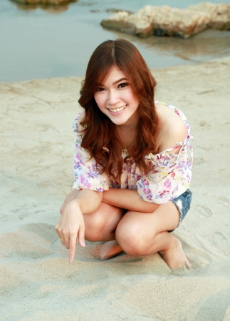 a portrait of beautiful woman on the sand with river photo