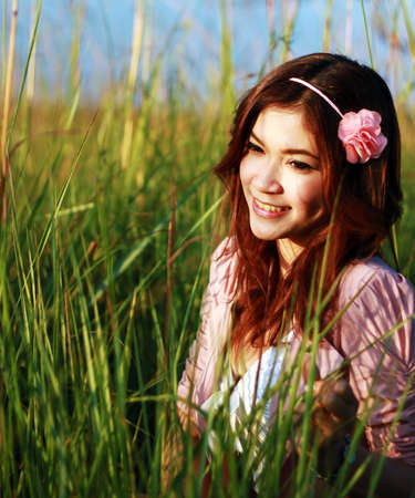 Portrait of beautiful young Asian girl in the grass photo