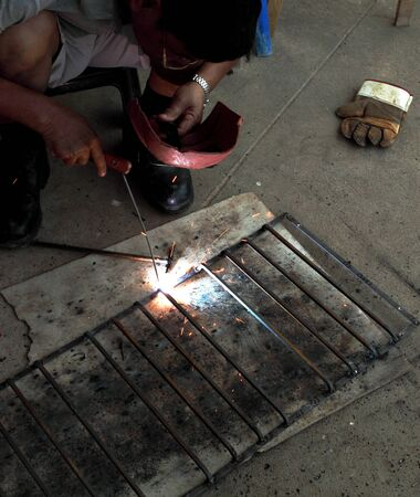 worker welding connecting square bar  without gloves photo
