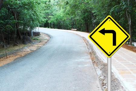 Gire a la izquierda en se�al de advertencia de un camino de la curva photo