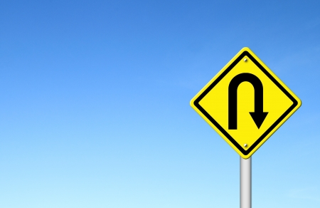 uturn: Yellow warning sign u-turn roadsign with blue sky background blank for text Stock Photo