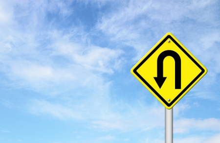 Yellow warning sign u-turn roadsign with blue sky background blank for text Archivio Fotografico
