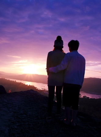couple is standing on the cliff silhouetted in the sunrise photo