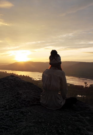woman sitting on a cliff with sunrise photo