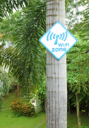 laptop outside: Wi-Fi zone sign on tree in the garden