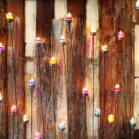 aromatic candle and wooden wall background photo