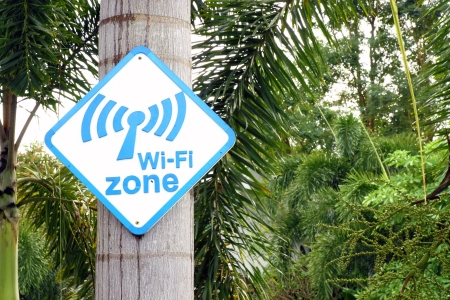 laptop outside: Wi-Fi zone sign on tree in the park Stock Photo