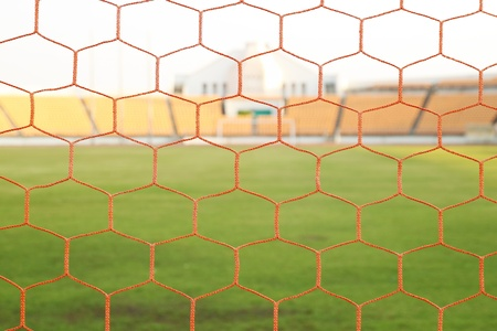 red net soccer goal football and green grass field in stadiun Stock Photo