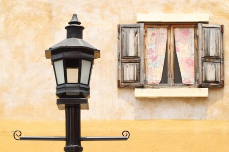 ancient lamppost with vintage window and wall background photo