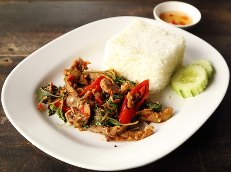 A fresh dish of Thai style food, Fried pork with sweet basi and white jasmine sticky rice photo
