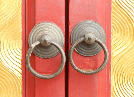 rusted knocker of red door , chinese style photo