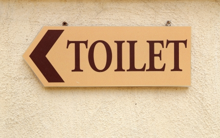 toilet sign with arrow on the wall photo