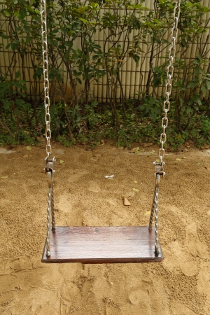 close-up wooden swing set on the playground photo