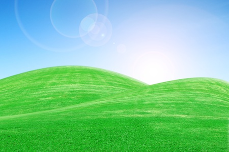 sunrise over green grass hills with blue sky photo