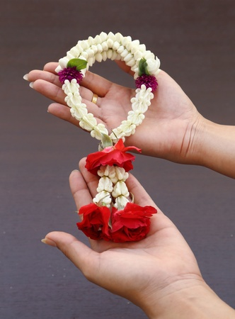 Garland of jasmine flower on hand with wood background photo