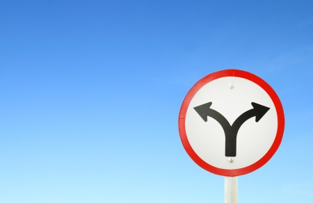 fork junction traffic sign with blue sky blank for text photo