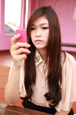young worried woman holding mobile phone photo