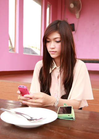 young beauty woman holding mobile phone in restaurant  photo