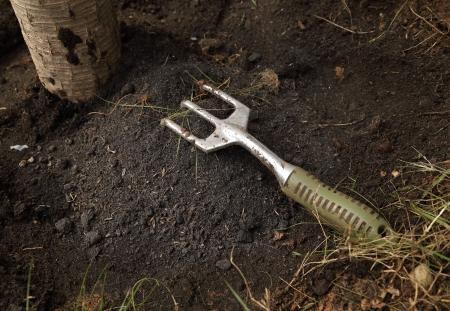 small gardening fork on the soil photo