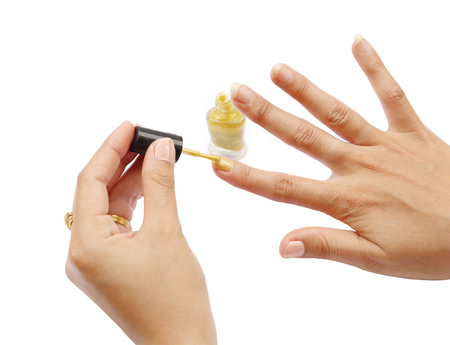 female hand with a golden nail polish on white background  photo