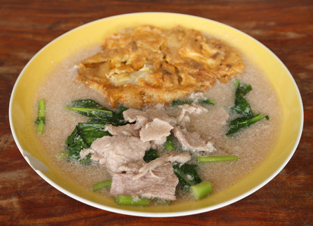 Fried noodle with omelet and pork and kale in gravy  photo