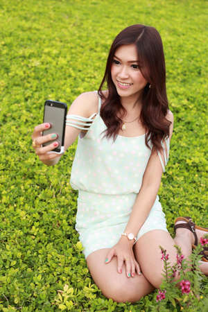 young woman taking a self portrait by using mobile phone in the garden photo