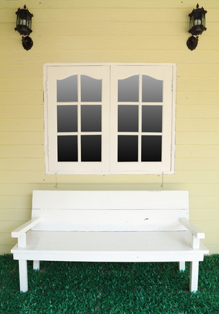 wooden bench for rest under the window (vintage style) photo