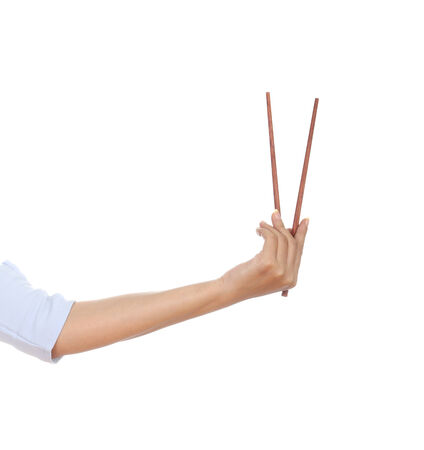 Chopsticks in a hand isolated on white background photo