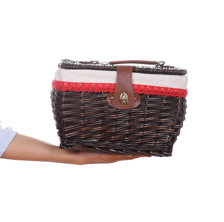 hand with weave wicker basket bag isolated on white background photo