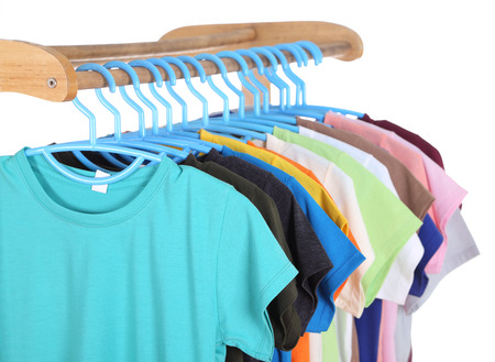 t-shirts hanging on hangers isolated on white background photo