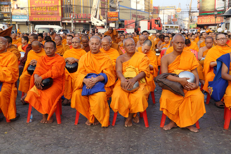 public offering: NAKHON RATCHASIMA, THAILAND - FEB 8:  International Alms Offering to 12,357 monks, Unidentified monks wait the auspicious to walk to the public alms in the occasion celebrating 357-year anniversary of Nakhon Ratchasima city at Chumphon Rd. in Nakhon Ratch