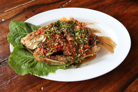 Fried ruby fish topped with sweet,sauer and hot sauce on dish photo
