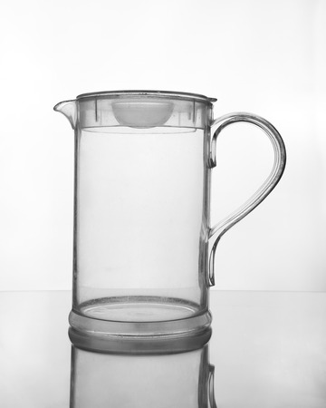 empty glass jug on glass table (gray scale) photo
