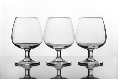 three empty wine glass on glass table (gray scale) photo