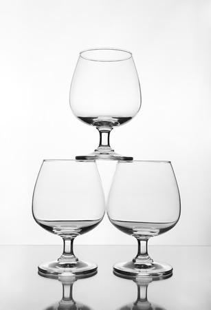 stack of empty wine glass on glass table (gray scale) photo