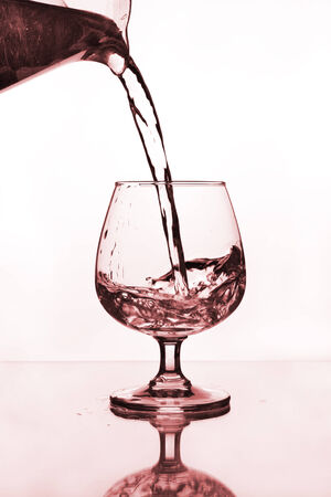 water jug pouring to wine glass on glass table photo
