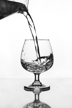 water jug pouring to wine glass on glass table (gray scale) photo