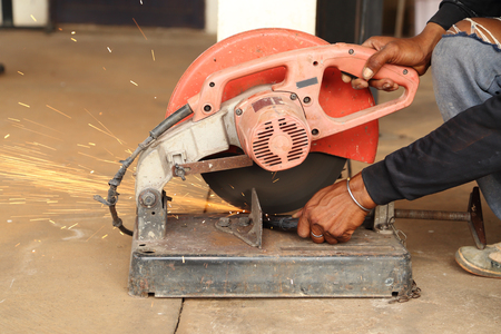 Worker cutting metal with cutting machine photo