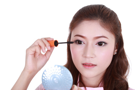 woman face with mascara brush with mirror isolated on white background photo