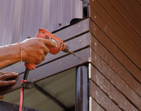 carpenter at lock installation with electric drill into construction photo