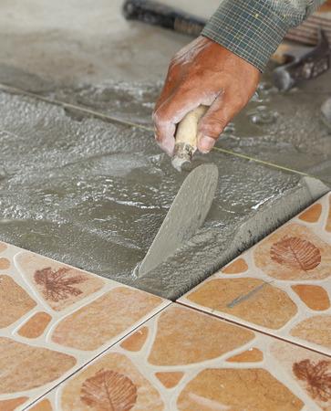 renovation - handyman laying tile, trowel with mortar