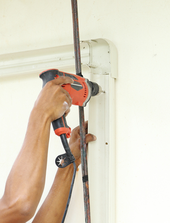 worker using drill to attach panel to wall photo