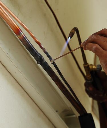 Air conditioner repairman welding copper pipes
