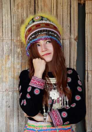cogitate: Traditionally dressed Mhong hill tribe woman thinking in the wooden cottage
