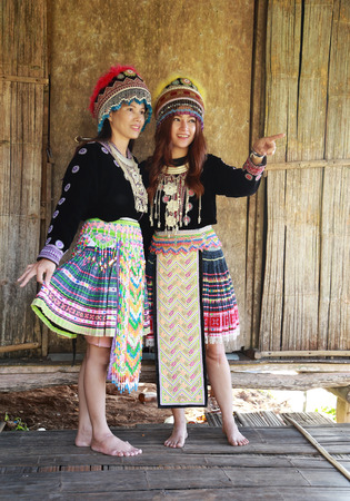 Traditionally dressed Mhong hill tribe woman in the wooden cottage photo