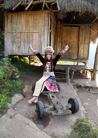 Traditionally dressed Mhong hill tribe woman at the wooden cottage photo