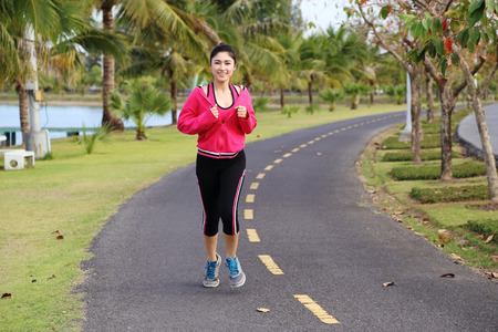 young healthy asian woman running in the park photo